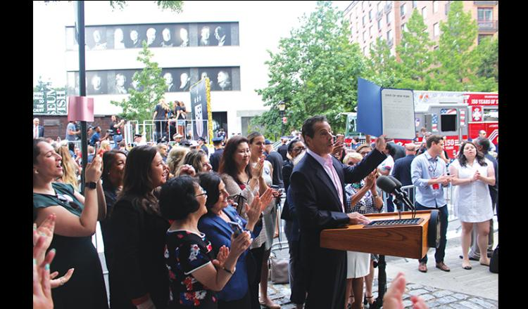 Executive Vice President Rebecca Damon looks on as New York Gov. Andrew Cuomo on holds up newly signed legislation that expands the state's equal pay laws July 10.