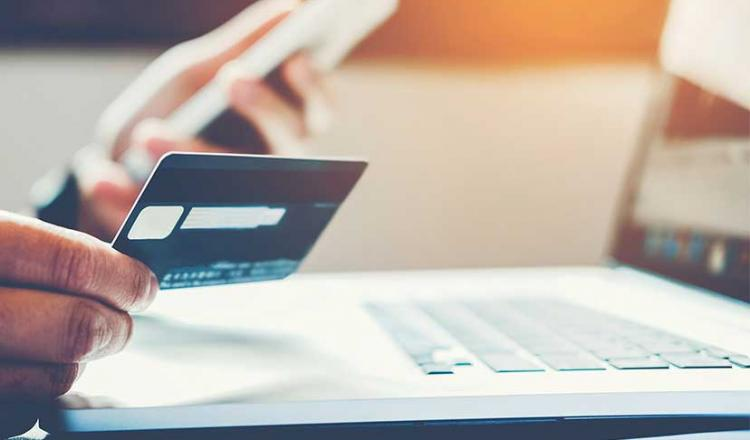 mano que sostiene una tarjeta de crédito en una mano y un teléfono en la otra flotando sobre una computadora portátil