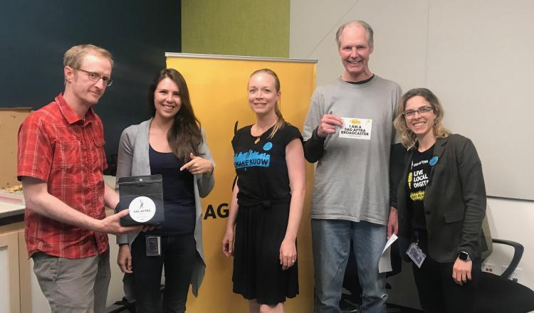 "Ryan holding a black box with a SAGAFTRA magnet, Walters pointing to black box, Dornfeld smiling for the camera, O'Grady holding a ""I AM A SAG-AFTRA BROADCASTER"" sticker with Browning smiling next to him."