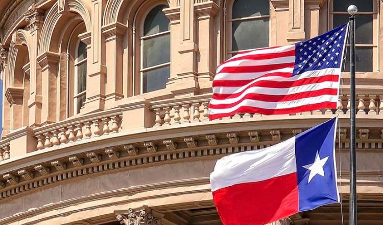 Imagen de la bandera estadounidense y la bandera del estado de Texas fuera del edificio del capitolio