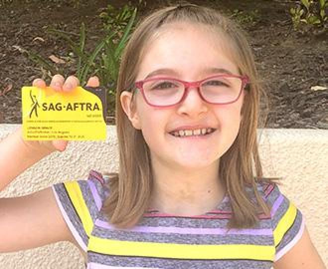 Young Grace wearing grey white and yellow shirt and red circle glasses holding member card