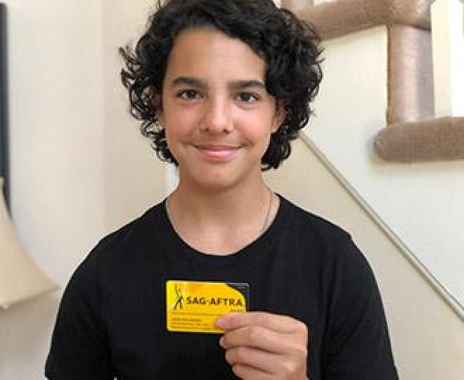 Young member Medina wearing black shirt with staircase in the background holding member card