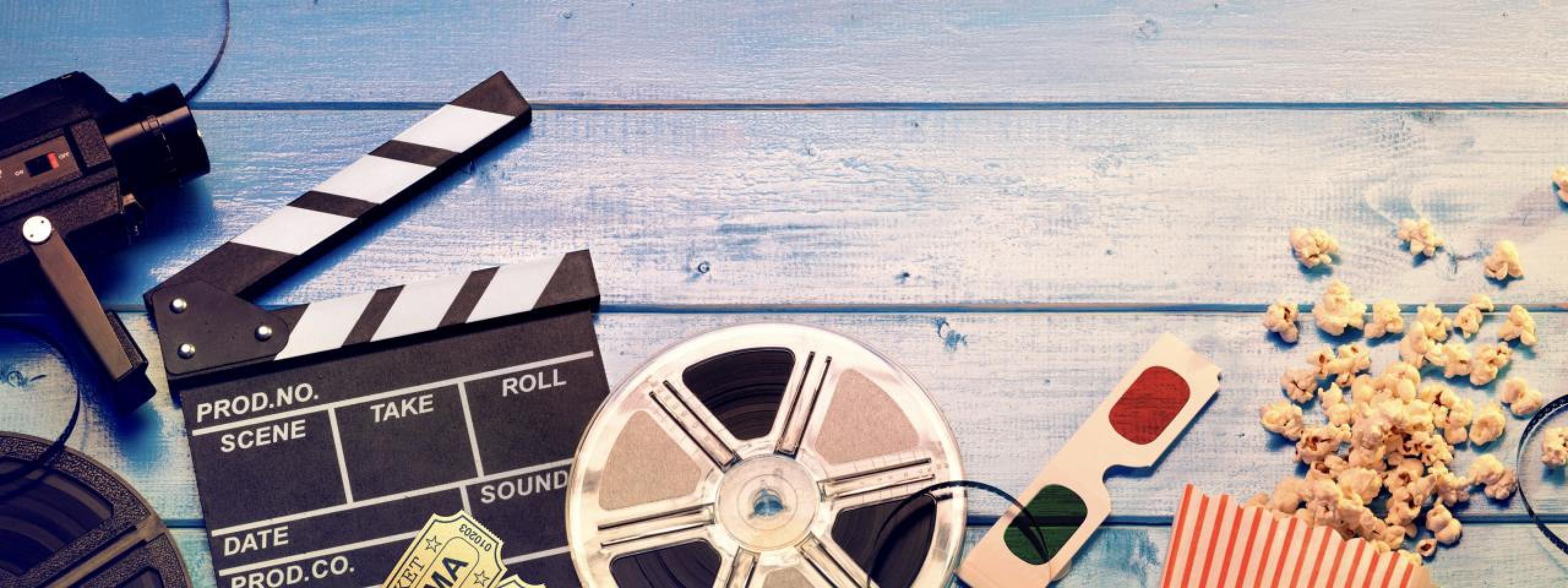 Film Canister, gafas 3D y claqueta en una mesa de madera azul