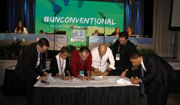 DCI in suite next to Gabrielle Carteris leaning over a table, Ochoa pointing to the crowd with his righ thand, Treviño in white leaning over a table signing papers, Calva leaning over table in a black shirt and DW in a suite
