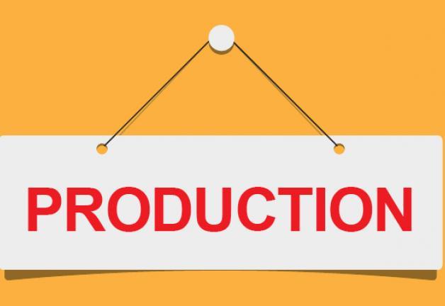 """""""PRODUCCIÓN"""" en rojo sobre una hoja blanca que cuelga de un alfiler blanco con fondo naranja"""