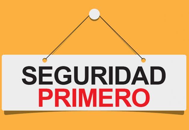 """""""SEGURIDAD PRIMERO"""" en rojo sobre una sábana blanca colgando de un alfiler blanco con fondo naranja"""