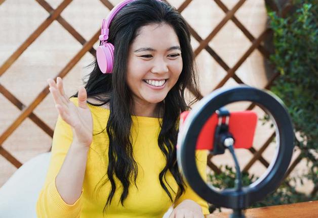 Imagen de mujer en top amarillo usando audífonos mirando móvil con anillo de luz detrás.
