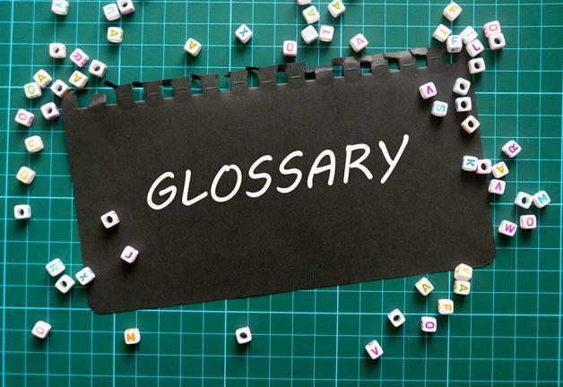 'GLOSARIO' en texto blanco sobre papel mate negro sobre una tabla de cortar verde
