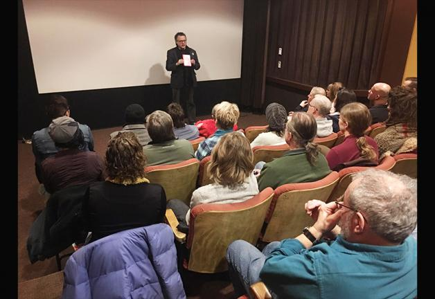 SAG-AFTRA Seattle Local President Rik Deskin stands in front of group of seated individuals in a small movie theater.