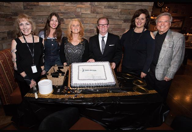 Six individuals--four females and two males--stand at a table where a cake is in the center.