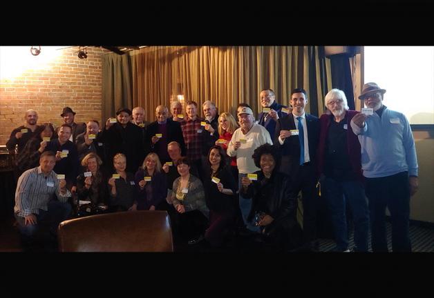 Foto grupal de miembros de SAG-AFTRA con sede en Pittsburgh que sostienen sus tarjetas sindicales.