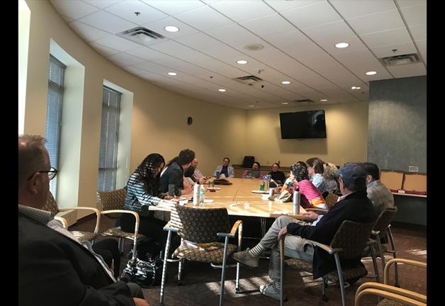 Los miembros del Twin Cities Local están sentados alrededor de una mesa y conversando entre ellos.