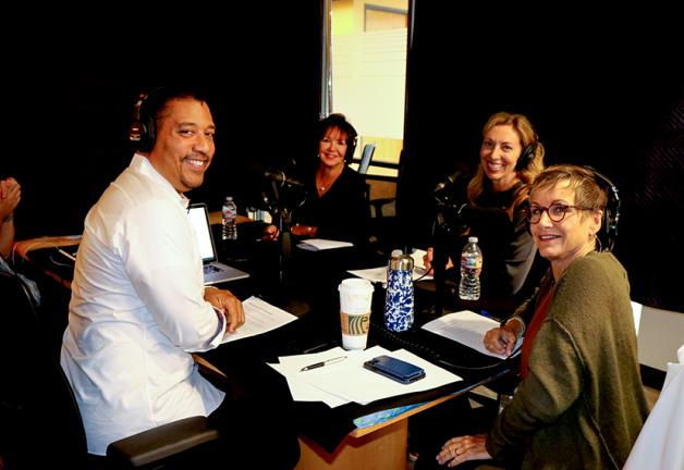 David white sitting at a table with headphones wearing a white button up smiling sitting next to Carteris in a olive Cardigan and headset. Bender and Harcharic sit side by side and across the table from White with headphones on.