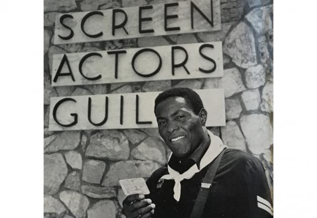 "Johnson holding SAG card in front of ""Screen Actors Guild"" sign"