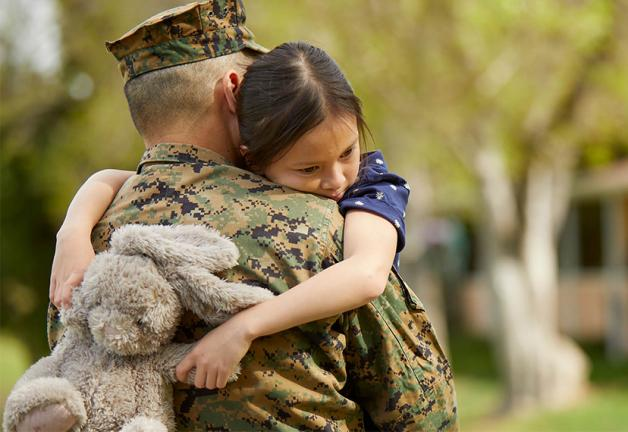 Dressed Military personnel carrying a young girl whose arms are wrapped around Military personnel holding a light grey stuffed bunny
