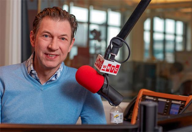 Hake in blue v-neck sweatshirt with a blue plaid collar button up underneath smiling with a WNYC microphone off to his right. Background: Studio