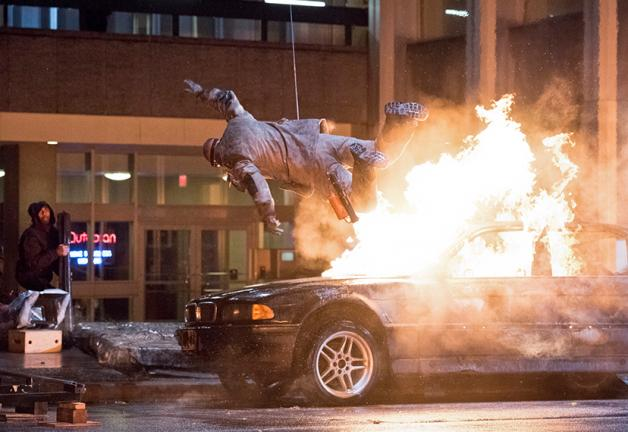 """Male stunt performer is teethered above a car on fire on the set of CW's """"The Flash."""""""