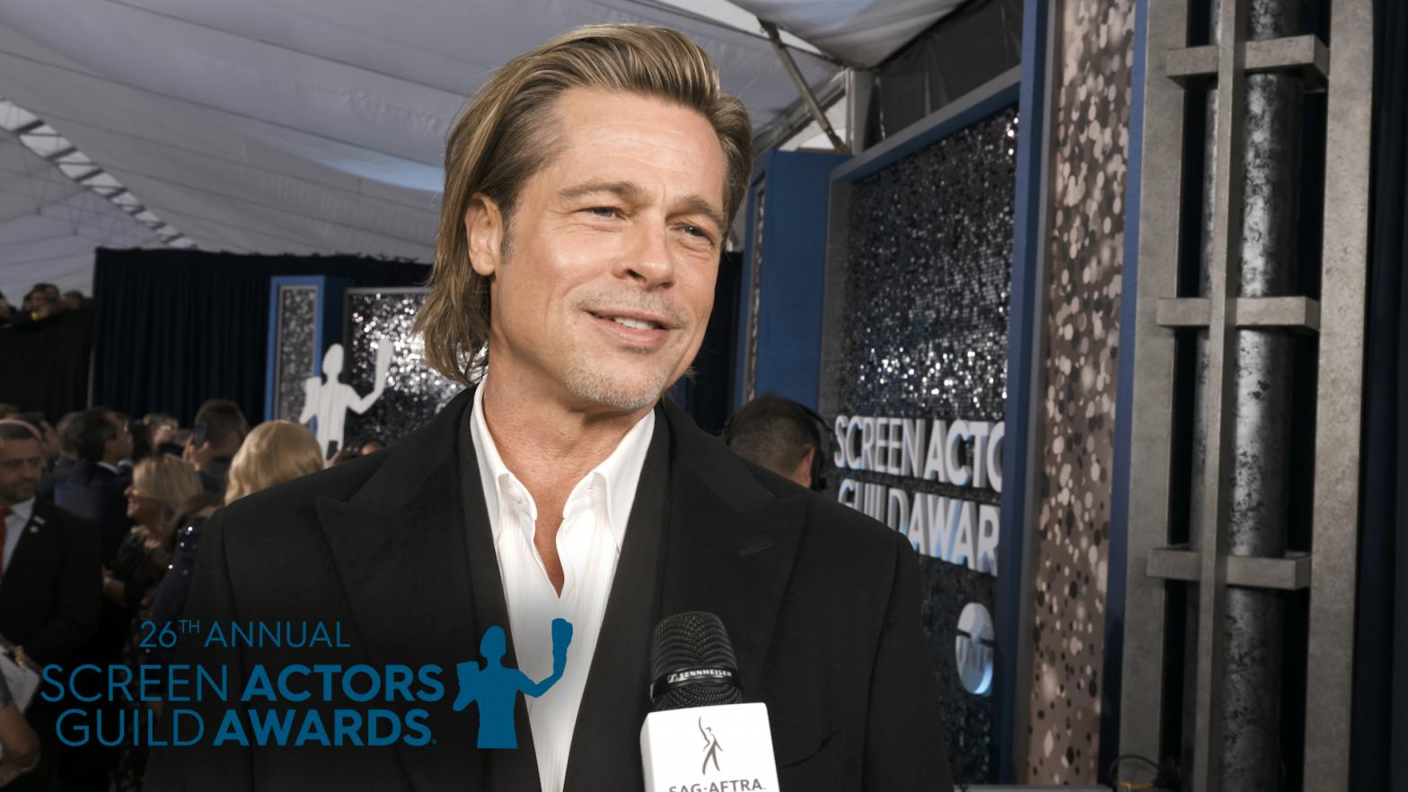 "Brad Pitt in a white button up and black tux looking slightly off camera to his right at the interviewer. Behind him is the ""silver"" carpet full of people at the 26th Annual Screen Actors Guild Awards"