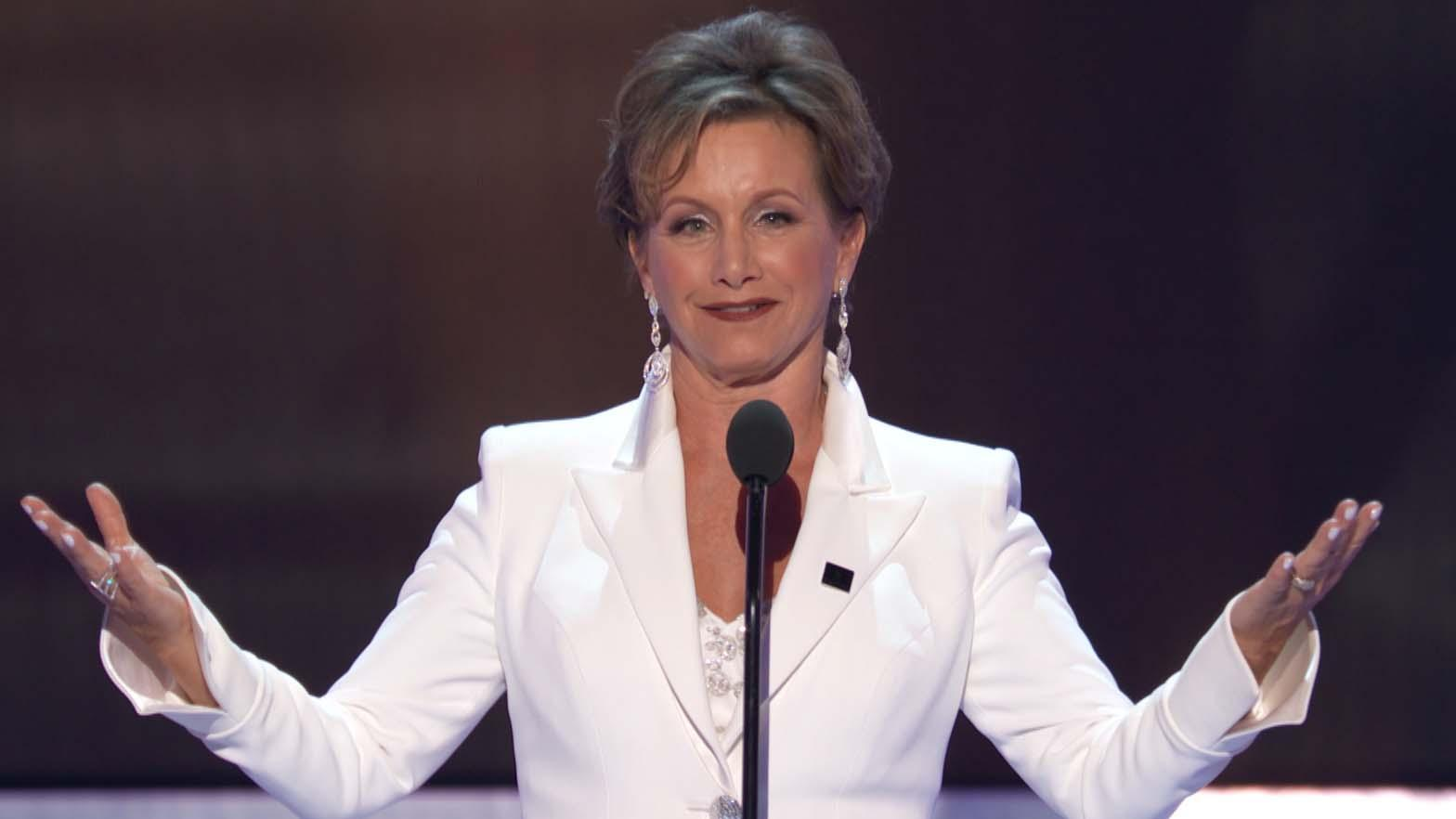 Gabrielle Carteris on stage in an all white suite